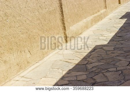 Ancient Street Background With Adobe Material Walls And Paving Stones. Near East Or Central Asian Ru