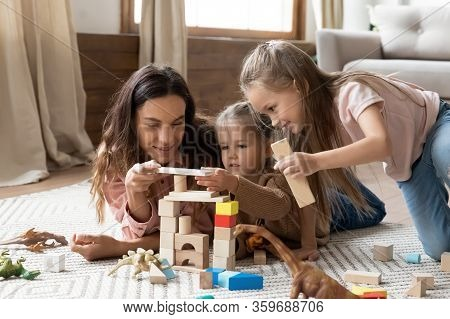 Smiling Mixed Race Babysitter Playing With Children.