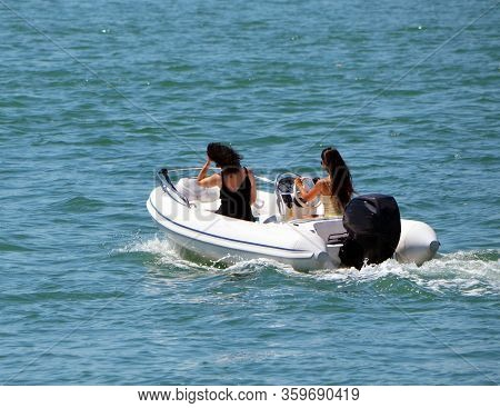 Two Attractive Young Women Cruising Off Miami Beach,florida In A Small Upscale Pontoon Motorboat Pow