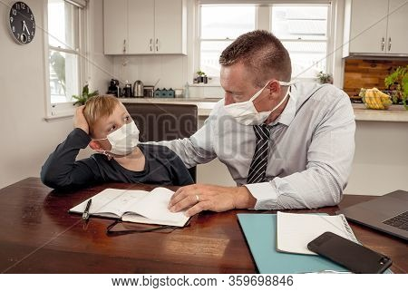 Covid-19 Pandemic School Lockdowns And Self-isolation. Worried Parent Helping Son Studying At Home