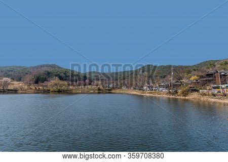 Chungju, South Korea; April 3, 2020: Pond Under Beautiful Blue Sky With Cars And Buses Parked Along
