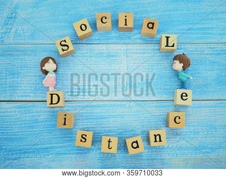 Top View Of Wooden Block With Word Social Distance And Couple Toy Kissing On Blue Wood Texture Backg