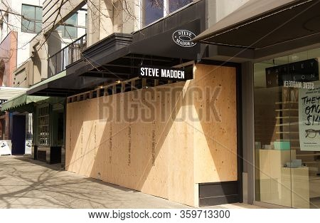 Vancouver, Canada - April 2, 2020: Vancouver Shops Have Boarded Up Their Storefronts With Wood Follo