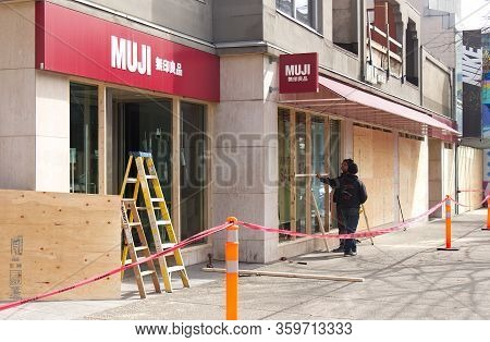 Vancouver, Canada - April 2, 2020: Workers Is Boarding Up The Storefront Of Famous Shop