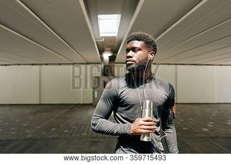 Portrait Of Serious Young Black Sportsman Listening To Music With Earbuds And Drinking Water