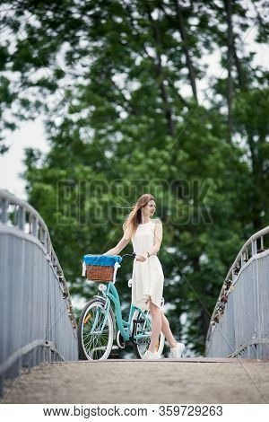 Cheerful Maiden In A Light Dress With Long Hair Standing With A Vintage Blue Bike And Enjoing Nature