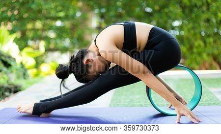 Asian Woman Practice Yoga In A Garden