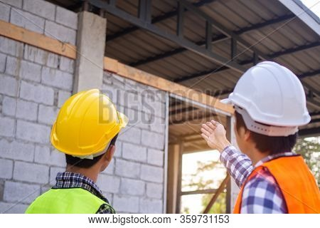 The Inspector Is Checking With The Checklist And Pointing Out The New Building With The Structure An