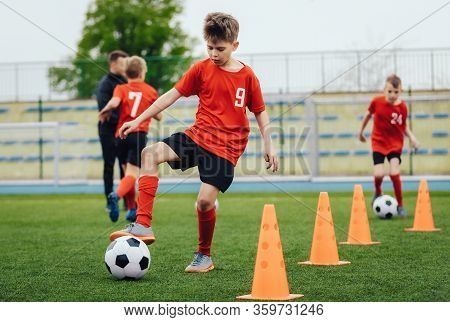 Boy In Children's Soccer Team On Training. Kids Practicing Outdoor With A Soccer Balls. Training Foo