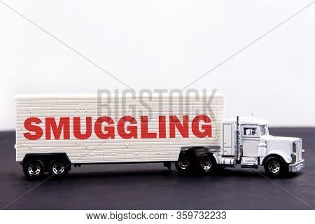 Smuggiling Word Concept Written On Board A Lorry Trailer On A Dark Table And Light Background