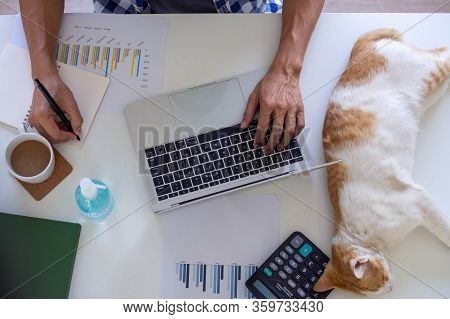 A Man Working Or Study Online In The Living Room On The Sofa. Due To The Spread Of The Virus Covid-1