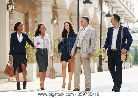 Happy Business People Walking In The Street, Discussing Work And Joking Around After Work