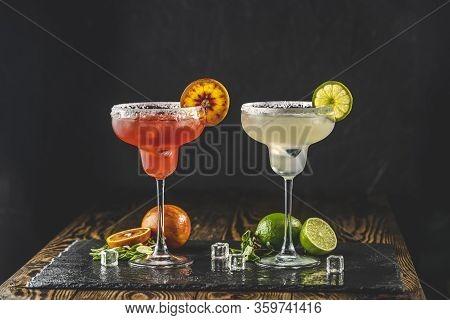 Frozen Lime Margarita And Blood Orange Margarita Cocktail Mix In Salt Rimmed Glasses Garnished. Dark