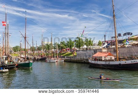 Kiel, Germany - June 24, 2019: Canoe In Between Old Ships In The Harbor Of Kiel, Germany