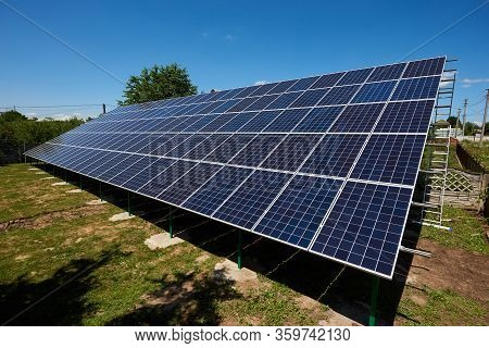 Sideview Of Huge Solar Panels Installed On Outdoors Opened Space. Modern Solution For Natural Resour