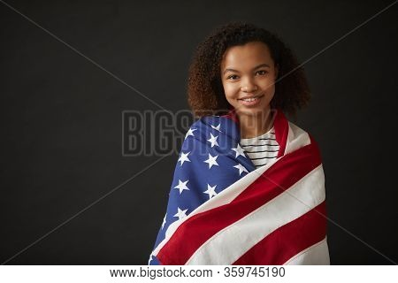 Waist Up Portrait Of Young African-american Girl Wrapped In American Flag While Standing Against Bla