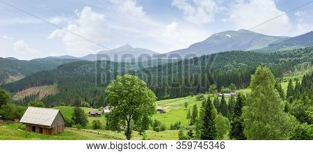 Mountain Landscape With Outbuildings And Hayfields On Meadow Among The Forest On A Foreground Agains