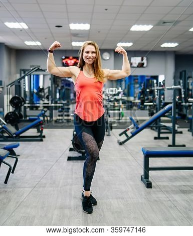 Athletic Woman Showing Muscles In Gym. Fit Girl. Fitness Model Full Lenght. Gym Background.