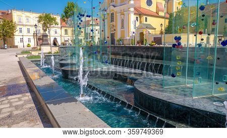 Gyor Hungary 06 30 2019: Young Woman Looking At The Fountain At The Gate Of Vienna Gate Square In Th