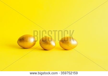 Gold Decorative Eggs Rolling  And Knock Each Other A Yellow Background. Spring Holiday Concept. Copy