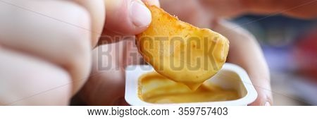 Close-up Of Persons Hand Dipping Fried Potato In Tasty Cheese Sauce. Yummy Snack For Quick Break In