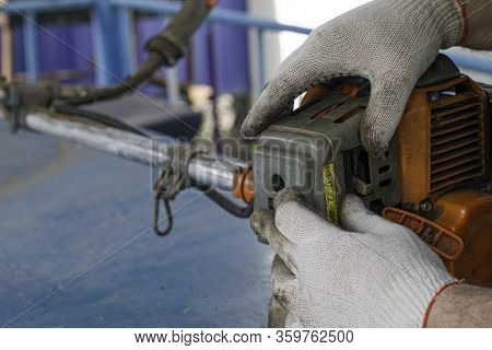 A Master In Working Gloves Repairs The Engine Of The Old Gas Trimmer Removes The Cover Of The Carbur