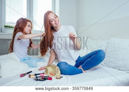 Cute Foxy Hair Little Girl Applying Make Up And Doing Hairstyle To Redhaired Ginger Mother At Bedroo