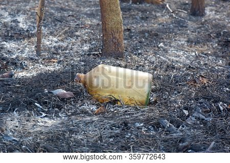 Bottle From Flammable Liquid On Ashes Of Burnt Grass After Wildfire Close Up View. Humanity Blame In
