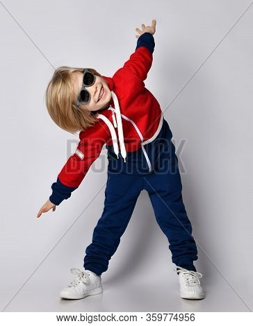 Happy Active Frolic Blond Kid Boy In Blue And Red Sportswear Hoodie, Pants And Sunglasses Is Playing
