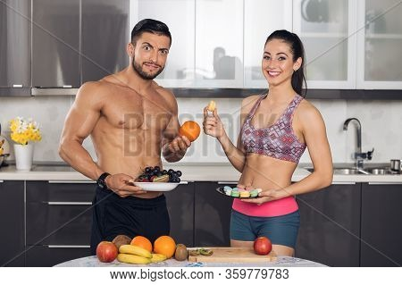 Young Fit Couple In Kitchen With Fruits And Macarons, The Bou Is Astonished About Girl Choosing Maca
