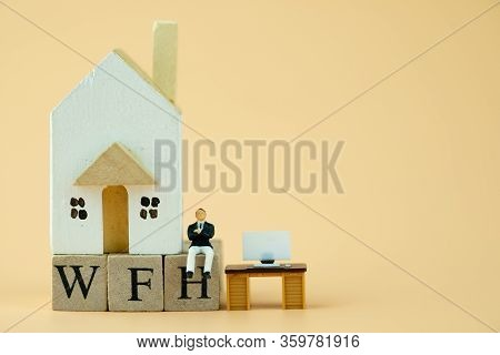 Miniature People: Businessman Sit On Wood Blocks Of Wfh With Wooden Home And Miniature Office Table