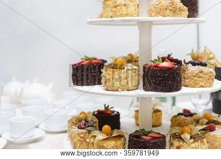 Chocolate And Vanilla Cakes With Berries, Physalis And Strawberries On A Three-tier Dessert Stand, C