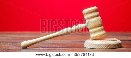 Judge's Hammer On A Red Background. The Judicial System. Norms, Rules And Laws. Conflict Resolution