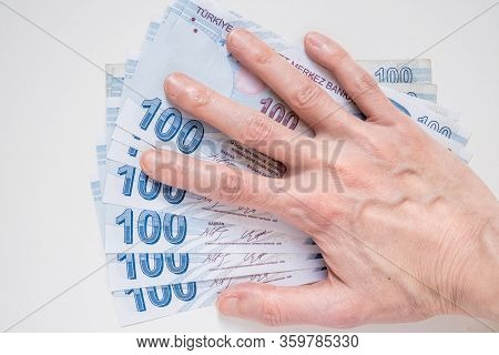 Female Hand On A Bunch Of 100 Turkish Lira (try) Banknotes Isolated On White Background.