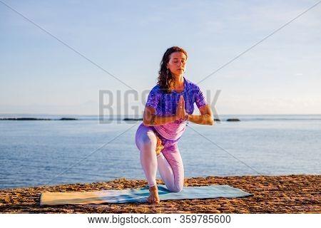 Attractive Woman Practicing Vatyasana, Variation Of Vrikshasana, Tree Pose.  Balance And Concentrati