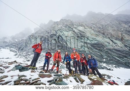 Male Alpinists Standing On Rocks And Stones While Taking Break From Hiking In Winter Mountains. Hike