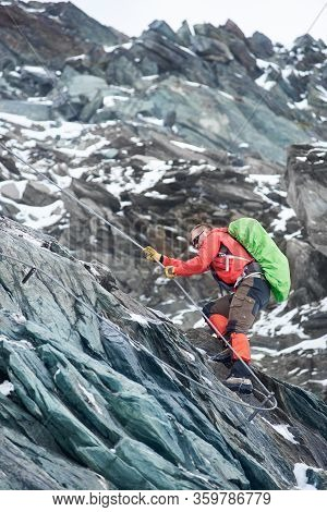 Brave Mountaineer In Sunglasses Holding Rope While Climbing Alpine Ridge. Male Alpinist With Backpac