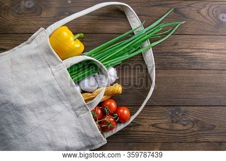 Woven Bag Of Different Health Food On Dark Wooden Table Background. Green Onion, Garlic, Tomato And