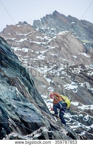 Mountaineer With Backpack Using Fixed Rope To Climb High Rocky Mountain. Man Climber Ascending Alpin