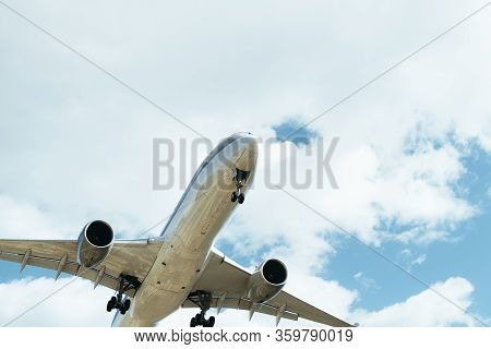 Front Of A Commercial Flight In A Cloudy Sky Seen From Below With The Landing Gear Deployed, Travel