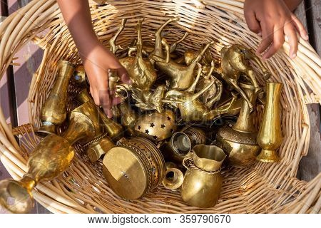 Child Playing With A Variety Of Brass Collectible Objects