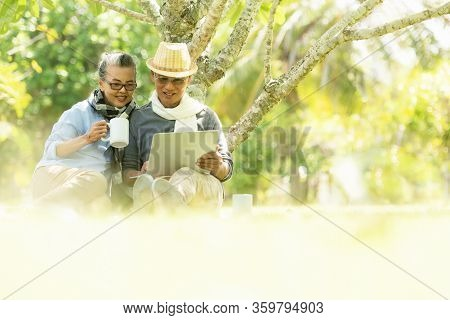 Asian Lifestyle Senior Elderly Retire Couple Drinking Coffee And Work From Home Online  In The Natur