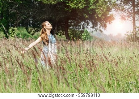 Beautiful Young Woman Stands In A Field And Raises Her Hands Up. Herbalist. Freedom.