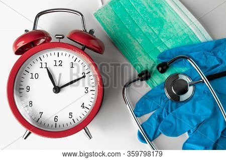 Red Clock, Green Protective Face Mask, Stethoscope And Gloves On A White Background.