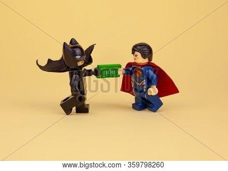 Ukraine, Kyiv - April 6, 2020: Lego Minifigures. Batman Gives Superman A Hundred Dollars. Get Paid I