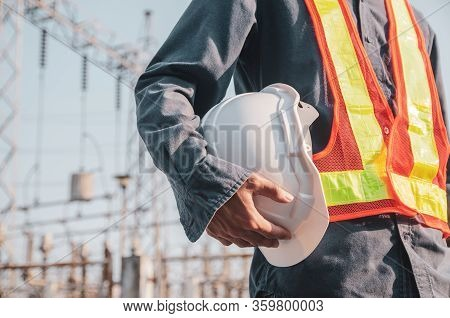 White Safety Helmet Is In The Hands Of An Electrician.