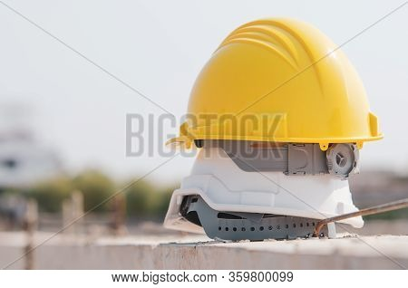 White And Yellow Helmet Placed On The Construction Site.
