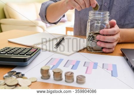 Men Sitting In House, Put Coin Into A Glass Jar And Calculate Personal Saving And Expense For Future