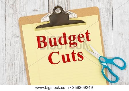 Budget Cut Message On Yellow Lined Paper With Scissors On A Clipboard On Weathered Whitewash Wood