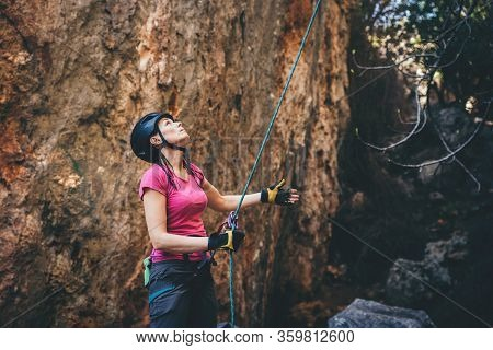 Young Athletic Woman Belay Her Partner Who Climbs  An Overhanging Rock With Rope In Turkey. Sport Cl